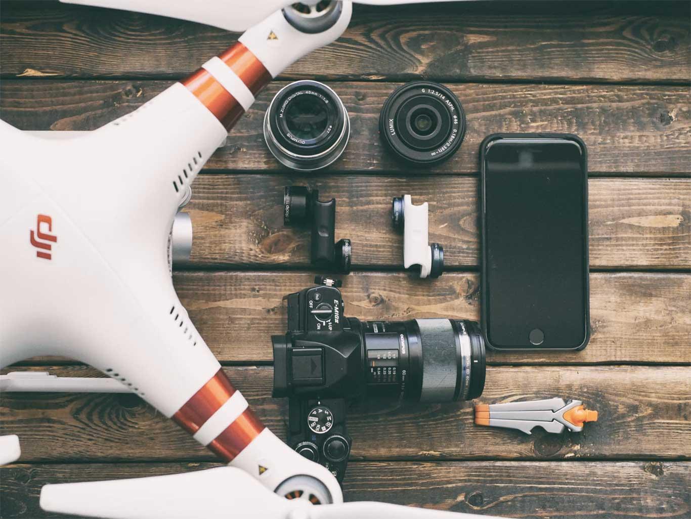 Drone, kamera og mobiltelefon på en bænk set oppe fra